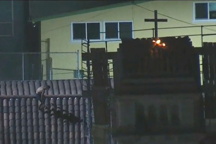 Man in underwear torches cross on top of church, attempts to flee by jumping across rooftops