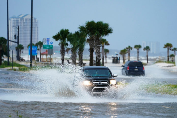 Cars drive through flood waters along route 90 as outer bands of Hurricane Ida arrive.