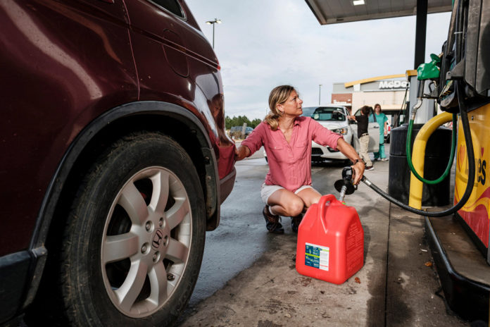 Jennifer Tate fuels up a gas can as she prepares for the arrival of Hurricane Ida in Pass Christian, Mississippi.