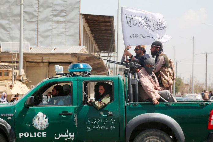 Taliban fighters ride on a vehicle.