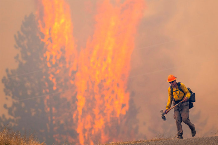 After walking down a gravel road to do recon on a fire cresting into the trees, a wildland firefighter grimaces as he walks back to his crew on Thursday, Aug. 12, 2021