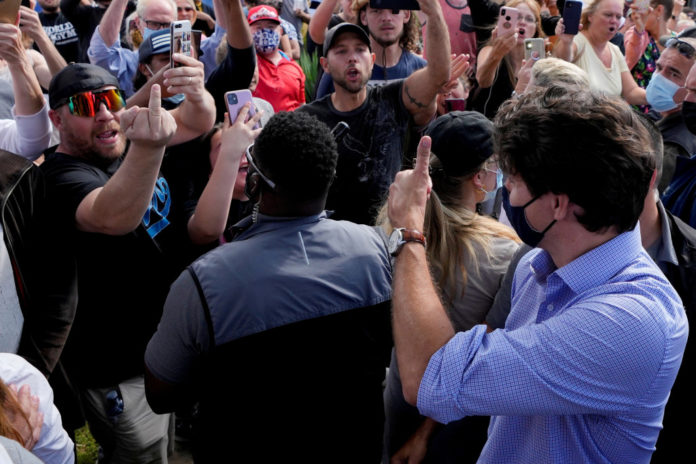 Justin Trudeau hit by gravel from COVID vaccine protesters at campaign stop